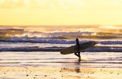 Het lopen van Surfer zonsondergang Stock Foto's