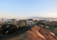 Het lopen van weg op de kam van de berg Blahnukur bij zonsondergang, Landmannalaugar-gebied, Fjallabak-Natuurreservaat, IJsland stock afbeeldingen