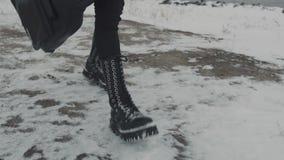 Het lopen in zwarte broek en zwarte rotsschoenen Sneeuwgrond stock footage
