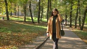 Het lopende mooie Kaukasische wijfje bevindt zich ontspannen die en bekijkt zon, achter groene bomen op voetpad in park wordt ver stock footage