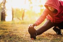 Het lopende uitrekken zich Vrouw het uitrekken zich been als opwarming vóór looppas w stock afbeelding