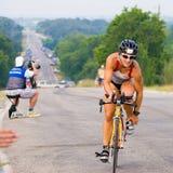 Het losmaken van de riem op haar fietsschoen vóór de looppas in een triatlon Stock Foto