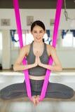 Het lucht antigravity yogameisje in lotusbloem stelt op zijdehangmat Stock Foto