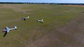 Het lucht schieten van drie zweefvliegtuigvliegtuigen op een gelijk groen gebied in een zonnige dag stock footage