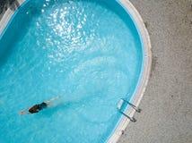 Het luchtbeeld over een blauw zwembad openlucht, een meisje geniet van de activiteit van de watersport royalty-vrije stock foto's