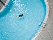 Het luchtbeeld over een blauw zwembad openlucht, een meisje geniet van de activiteit van de watersport stock fotografie