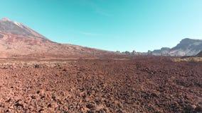 Het luchthommel schieten Woestijn vulkanisch landschap in rood Stenen en een berg met een vulkaan tegen de blauwe hemel E stock videobeelden