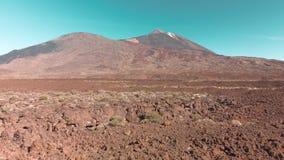 Het luchthommel schieten Woestijn vulkanisch landschap in rood Stenen en een berg met een vulkaan tegen de blauwe hemel E stock video