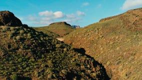 Het luchthommelbeeld van mooie overweldigende landschapsklippen schommelt pieken en valleien met een curvy weg op een zonnige dag stock foto's
