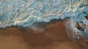 Het luchthommelschot van stroomversnellinggolven die op zandig strand als camera breken trekt zich terug stock video