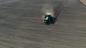 Het luchtonderzoek, hoogste mening, grote tractor met speciale materiaalritten door geploegd gebied van zwarte grond, vormt zelfs stock video
