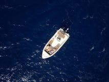 Het luchtonderzoek van een paar op een boot zonnebaadt samen op warm Royalty-vrije Stock Afbeelding