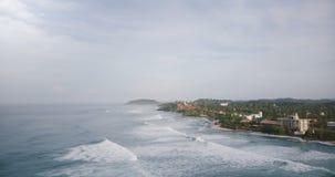Het luchtschot van de hommelluchtparade van idyllische schuimende oceaangolven die prachtige tropische toevluchtkust met gebouwen stock videobeelden