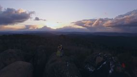 Het luchtschot van de kapper maakt de besnoeiing in openlucht bij zonsondergang Extreem kapsel op de bovenkant van de rots in stock footage