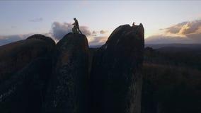 Het luchtschot van de kapper maakt de besnoeiing in openlucht bij zonsondergang Extreem kapsel op de bovenkant van de rots in stock video
