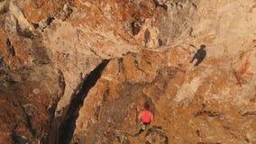 Het luchtschot van jonge moedige vrouwenklimmer beklimt neer de rotsonderbrekingen, valt en hangt op een veiligheidskabel Langzam stock footage