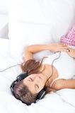 Het luisteren muziek op bed Stock Afbeeldingen