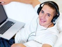 Het luisteren van de kerel muziek op laptop met hoofdtelefoon Stock Foto's