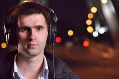 Het luisteren van de mens muziek bij nachtstraat Royalty-vrije Stock Foto