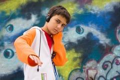Het luisteren van de tiener muziek tegen een graffitimuur Royalty-vrije Stock Afbeelding