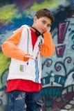 Het luisteren van de tiener muziek tegen een graffitimuur Stock Afbeelding