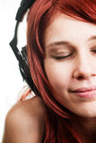 Het luisteren van de vrouw muziek bij hoofdtelefoons Stock Afbeelding