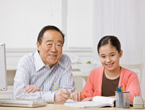 Het luisteren van het meisje aan grootvader verklaart thuiswerk Stock Afbeeldingen
