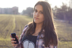 Het luisteren van het meisje aan muziek en toont haar mp3 speler Royalty-vrije Stock Fotografie