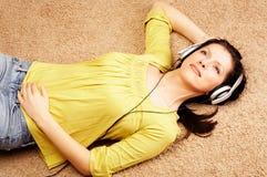 Het luisteren van vrouwen muziek in hoofdtelefoons Stock Foto