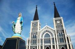 Het maagdelijke standbeeld van Mary met kerkachtergrond Royalty-vrije Stock Foto