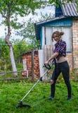 Het maaiende gazon van de vrouw Stock Foto