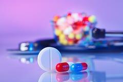 Het macrostilleven van pillen en van tabletten op viooltje stock afbeelding