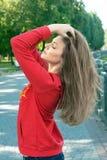 Het magere meisje houdt de gekruiste handen achter een hoofd royalty-vrije stock foto