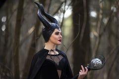 Het magische Maleficent Karakter Stellen met Oplichter in de Lente Leeg Bos royalty-vrije stock afbeelding