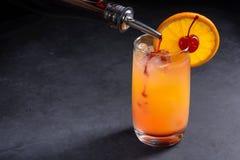 Het maken van de cocktail van de tequilazonsopgang Grenadine in een glas van ijs, jus d'orange en tequila langzaam wordt gegoten  royalty-vrije stock fotografie