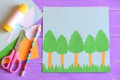 Het maken van de kaart van de Aardedag stap gids De kaart van de aardedag met bomen en gras, schaar, lijmstok, potlood, malplaatj Royalty-vrije Stock Afbeeldingen