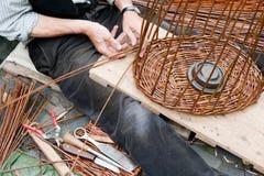 Het maken van een rieten mand Stock Afbeeldingen