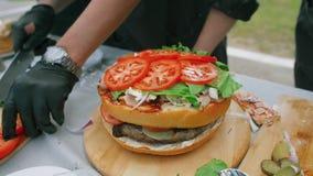 Het maken van een sappige grote hamburger met een dubbel broodje stock video