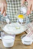 Het maken van gebakjedeeg Een bakker voegt een ei in de bloem toe Ingrediënten voor Baksel Royalty-vrije Stock Afbeeldingen