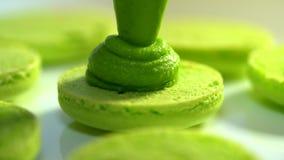Het maken van groene pistache macarons, het drukken van en het toevoegen van room die vanaf gebakjezak vullen Heerlijk en mooie m stock video