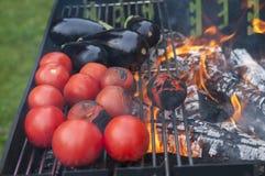 Het maken van groenten op grilltomaten en aubergines Royalty-vrije Stock Foto's