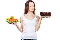 Het maken van harde keus tussen groenten en cake royalty-vrije stock foto