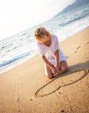 Het maken van hartvorm in zand stock afbeelding
