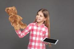 Het maken van juiste keus Meisje status geïsoleerd op grijs met gelukkige teddybeer en digitale tablet royalty-vrije stock fotografie
