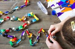 Het maken van Kerstmisdocument kettingen door jong geitje stock foto's