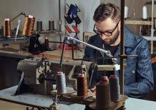 Het maken van kleren maak zitting bij lijst en het werken aan een naaimachine op de naaiende workshop stock foto's
