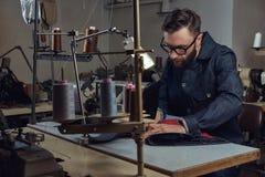 Het maken van kleren maak zitting bij lijst en het werken aan een naaimachine op de naaiende workshop royalty-vrije stock afbeelding