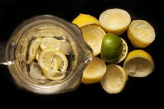 Het maken van limonade in een kruik of fles of kruik van gele citroenen en groene kalk met ijs stock fotografie