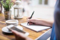 Het maken van nota's bij koffiepauze Stock Foto's