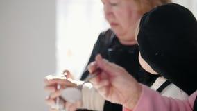 Het maken van pannekoeken Een oude vrouw die het deeg zouten Een klein meisje die op haar letten stock footage